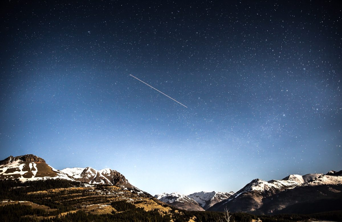 A mountain landscape, at night, with a comet shooting across the sky.