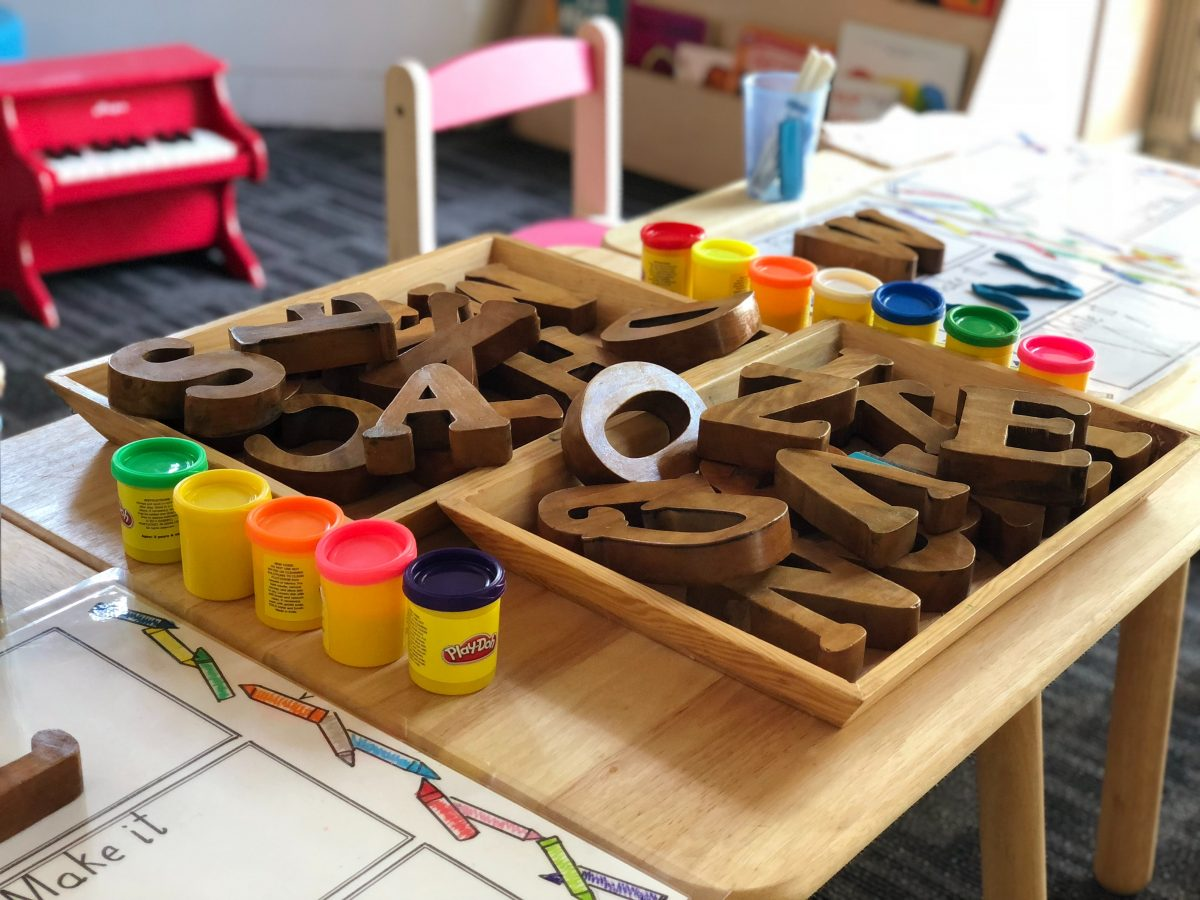 Play table for kindergarten student with manipulatives, play-doh, cut out letters. A red piano is visible.